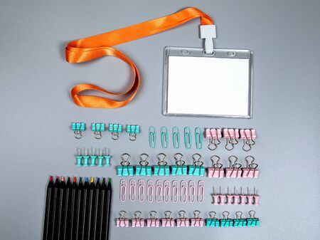 White empty staff identity mockup with lanyard. Binder clip and office supplies on a gray background. Pink and green Фото со стока