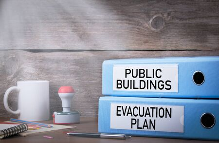Evacuation plan and public buildings. Two binders on desk in the office. Work and fire safety concept