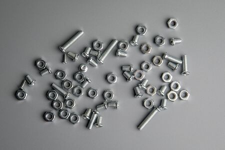 Metal bolts and nuts in a gray background. Chromed screw bolts and nuts. Set of Nuts and bolts Фото со стока