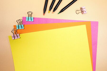 Yellow, empty sheet of paper mockup. Copy space. Binder clip with colored papers