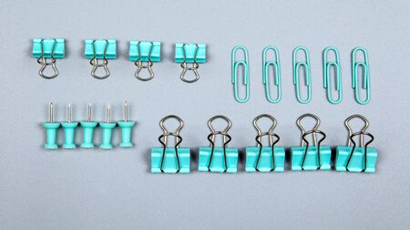 Binder clip and office supplies on a gray background Stock fotó