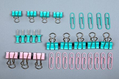 Binder clip and office supplies on a gray background. Pink and green