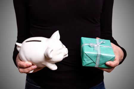 Woman holding piggy bank and gift box. Christmas gifts, shopping and savings concept