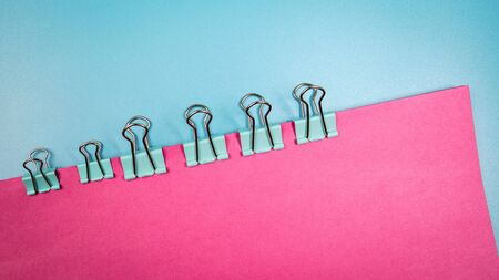 Binder clip with colored papers. Pink and blue background with copy space