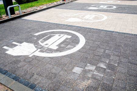 Parking symbol for electric cars being charged. Pavement of different colors Фото со стока
