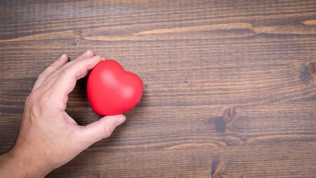 Heart shaped stress ball in a mans hands on a wooden background Stok Fotoğraf