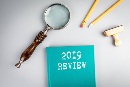 2019 Review concept. Green book cover and magnifying glass