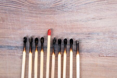 Be different, leadership, career and mentor concept. Burned matches on wood texture background