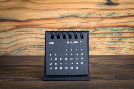 2020 January. Black paper calendar on a wooden table