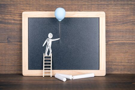 Instalation with white human figure with balloon on the stairs at the blackboard and chalks