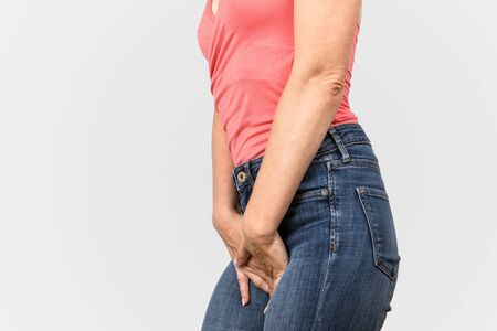 Gynecologic problems, urinary incontinence, female health. Woman holds hands between her legs Stock Photo