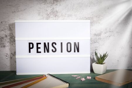 Pension. Years of work, Deserved rest, Savings and Health concept. White lightbox on a wooden table