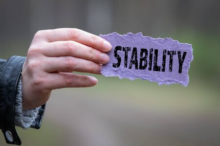 STABILITY. Text on the purple sheet in hand