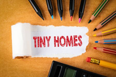 TINY HOMES. Text under torn paper. colored pencils and calculator
