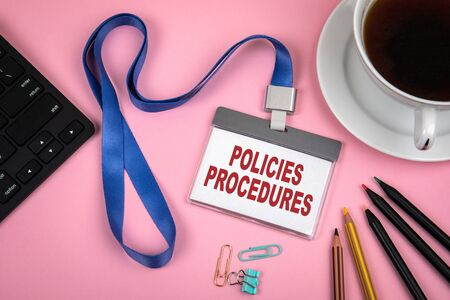 POLICIES and PROCEDURES concept. Staff Identity, cup of coffee and black computer keyboard on a pink background