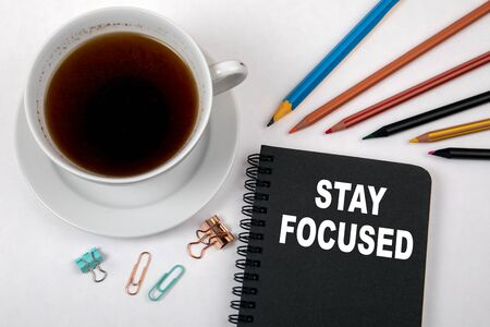 STAY FOCUSED concept. Black notebook and office supplies