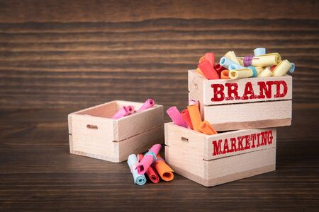 BRAND and MARKETING concept. Colored papr scrolls in wooden boxes on dark wooden background Stock fotó