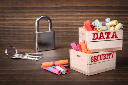 DATA and SECURITY concept. Colored papr scrolls in wooden boxes on dark wooden background