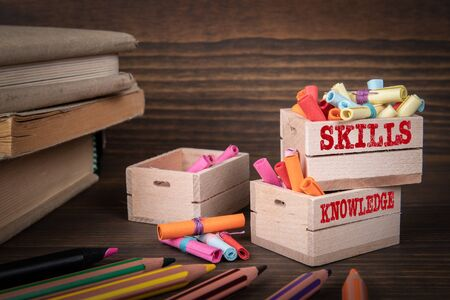 SKILLS and KNOWLEDGE concept. Colored papr scrolls in wooden boxes on dark wooden background