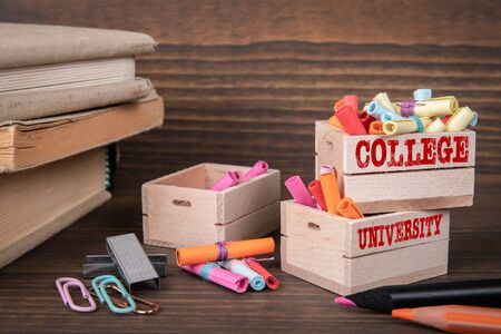 COLLEGE and UNIVERSITY concept. Colored papr scrolls in wooden boxes on dark wooden background