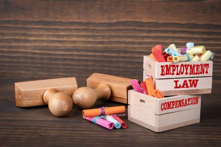 EMPLOYMENT LAW and COMPENSATION concept. Colored papr scrolls in wooden boxes on dark wooden background