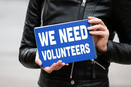 WE NEED VOLUNTEERS concept. Woman holding blue notebook