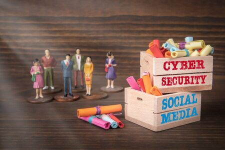 CYBER SECURITY and SOCIAL MEDIA concept. Colored papr scrolls in wooden boxes on dark wooden background Stock fotó