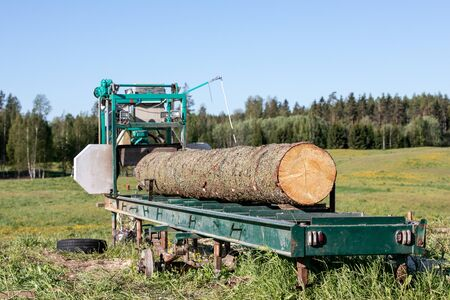 Mobile sawing equipment for logs in the open air. Rural landscape on a sunny day Banque d'images