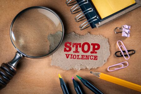 STOP VIOLENCE concept. Magnifying glass, stationery and note paper