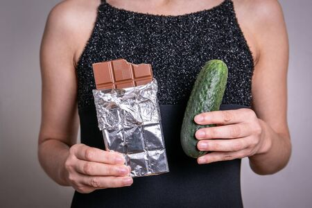 Diet concept. Choosing between sweet and nutritious chocolate and dietary cucumber