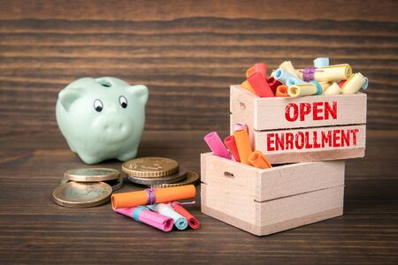 Open Enrollment concept. Colored papr scrolls in wooden boxes on dark wooden background