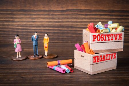 POSITIVE and NEGATIVE. Business and Emotions concept. Colored papr scrolls in wooden boxes on dark wooden background Stock fotó