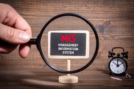 MIS, Management Information System concept. Hand holding magnifying glass