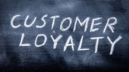 CUSTOMER LOYALTY concept. Black painted wood and inscription with chalk