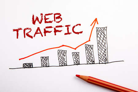 WEB TRAFFIC concept. Statistics graph with arrow. Red pencil on a sheet of paper