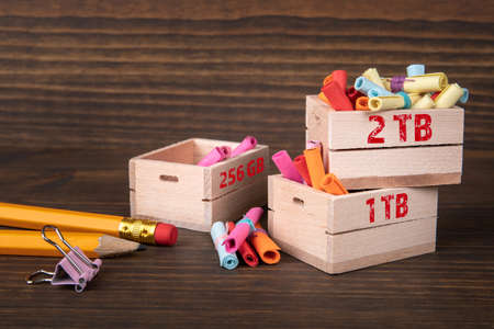 Email, digital memory and server concept. Colored papr scrolls in wooden boxes on dark wooden background.