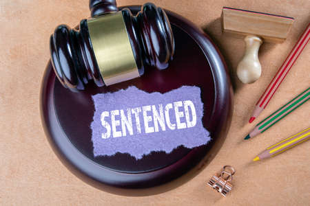 SENTENCED. Justice, judgment, legal services and court proceedings concept. Wooden judges hammer