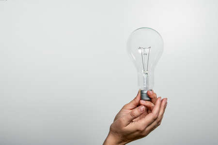 Light bulb in a womans hands. Free space for text and copy space