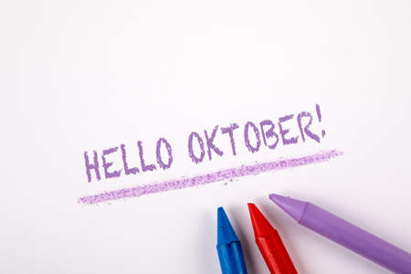 HELLO OKTOBER. Autumn, halloween, time planning and communication concept. Crayons on a white paper