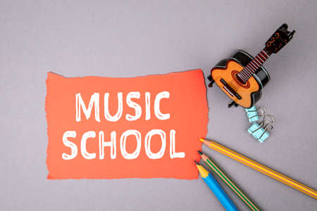 MUSIC SCHOOL. Miniature guitar and colored pencils on table