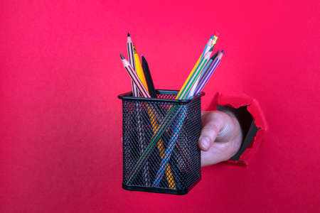 Stationery set in stand in hand on a red background Standard-Bild