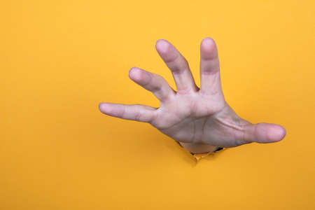 Hand reaches for help. Yellow paper background. Copy space