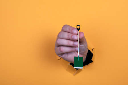 Miniature shovel in a womans hand. Work and diligence concept Standard-Bild