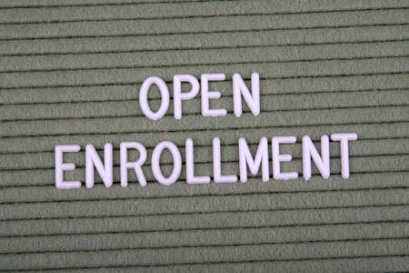 OPEN ENROLLMENT. White letters of the alphabet on a green background