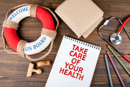 TAKE CARE OF YOUR HEALTH. Red stethoscope, stationery and lifebuoy with text
