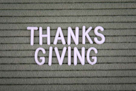 THANKS GIVING. White letters of the alphabet on a green background.