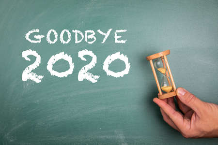GOODBYE 2020. Annual report, new years expectations, planning and goals concept. Sandglass in hand