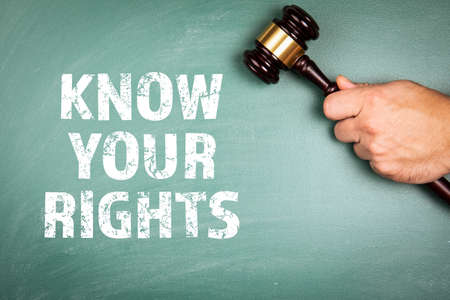 KNOW YOUR RIGHTS. In the hand of a judges wooden hammer. Green chalk board
