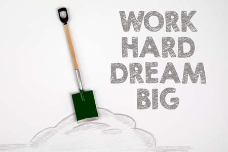 Work Hard Dream Big. Miniature shovel on a white paper Stock Photo