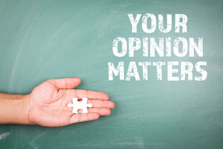 YOUR OPINION MATTERS. Piece of white puzzle in hand. Green chalk board